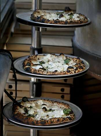 Pizzas baked in Jonathan Darsky's Del Popolo, a mobile pizzeria housed in a 25ft. shipping container, are seen on Thursday, June 7, 2012 at Mint Plaza in San Francisco, Calif. Photo: Russell Yip, The Chronicle