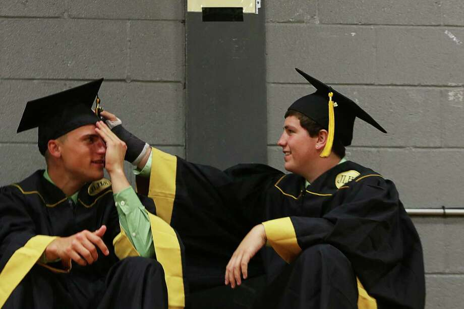 Mike Ross Connecticut Post freelance - Jonathan Law High School seniors Zach Pinto rights fixes the cap of friend Jake Saley  at stagging area for Tuesday's graduation. Photo: Mike Ross / Connecticut Post Freelance