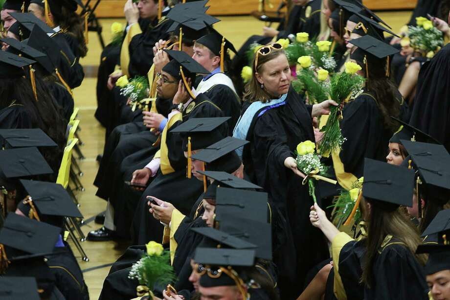 Mike Ross Connecticut Post freelance - Jonathan Law High School chemistry teacher Tracy Turcotte hands out yellow roses to students at stagging area for Tuesday afternoon commencement. Photo: Mike Ross / Connecticut Post Freelance