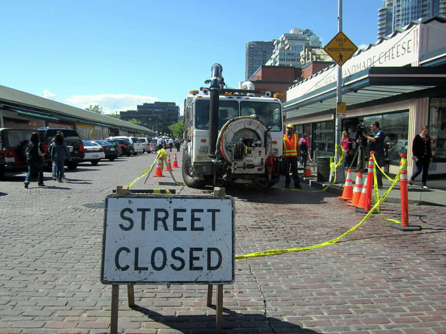 Seattle Public Utilities workers temporarily closed part of Pike Place and Pine Street after a sewer backup Tuesday afternoon. The backup was said to have been caused by grease that originated in a side sewer. Photo: Casey McNerthney/seattlepi.com