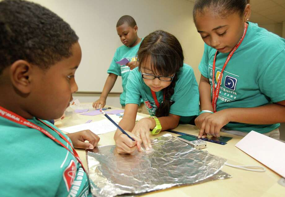 "Ethan Stueart, 12, left, Kevin Brinson Jr., 12, Giselle Yanez, 11, and Ramani Talley, 12, right, all of team Awesome, prepare their entry for  the ""Space Suit Challenge"" during the ExxonMobil Bernard Harris Summer Science Camp at the University of Houston, Tuesday, June 19, 2012, in Houston. The students had 20 minutes and had to use 4 different materials such as foil, wax paper, and Styrofoam to make a 14 layer space suit swatch. Photo: Melissa Phillip, Houston Chronicle / © 2012 Houston Chronicle"