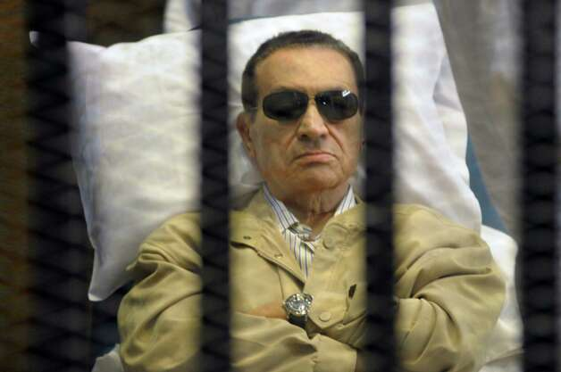 FILE - In this Saturday, June 2, 2012 file photo, Egypt's ex-President Hosni Mubarak lays on a gurney inside a barred cage in the police academy courthouse in Cairo, Egypt. An Egyptian prison official says Hosni Mubarak's health has taken a turn to the worst and is likely to be moved out of his prison hospital to a military facility nearby. The official said Tuesday doctors reported that the 84-year old former president has fallen unconscious. He said they have used a defibrillator to restart his heart, and have been administering breathing aid. (AP Photo, File) Photo: STR