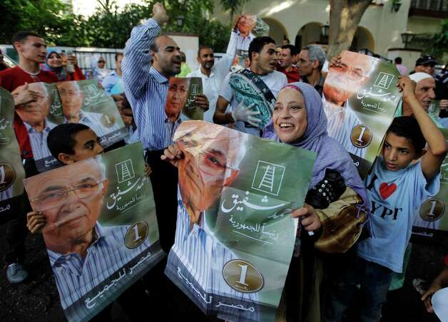 "Supporters of presidential candidate Ahmed Shafiq wave posters of him with Arabic that reads, ""Ahmed Shafiq for presidency, Egypt for all,"" in front of his campaign headquarters in Cairo, Egypt, Tuesday, June 19, 2012. A campaign spokesman for Hosni Mubarak's ex-prime minister said on Tuesday that Ahmed Shafiq has won the Egyptian presidential election, countering the Muslim Brotherhood's claims that its candidate was the winner. (AP Photo/Amr Nabil) Photo: Amr Nabil"