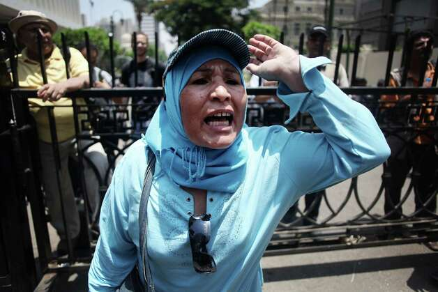 An Egyptian woman chats anti-Supreme Council for the Armed Forces (SCAF) slogans outside the Egyptian Parliament in Cairo, Egypt, Tuesday, June 19, 2012. The campaign of an Islamist who claimed victory in Egypt's presidential runoff says the Muslim Brotherhood and other political groups plan a mass demonstration later Tuesday to protest a military declaration seeking to curtail the powers of the next president. (AP Photo/Manu Brabo) Photo: Manu Brabo