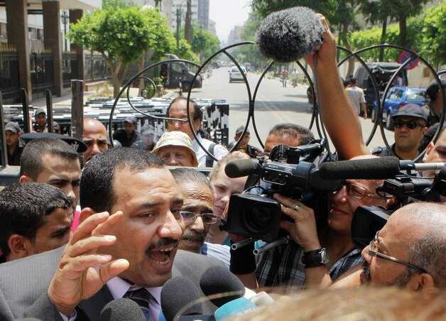 Former member of the Egyptian Parliament, Mohamed El-Omda, talks to reporters after he was prevented by security from entering his parliamentary office, shown in background, Tuesday, June 19, 2012.  Egypt's highest court has ordered the country's Islamist-dominated parliament dissolved, saying its election about six months ago was unconstitutional. (AP Photo/Amr Nabil) Photo: Amr Nabil