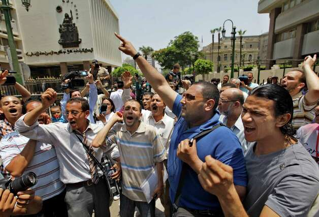 "Egyptian activists shout slogans against military rule in front of the parliament compound in Cairo, Egypt, Tuesday, June 19, 2012.  Egypt's highest court has ordered the country's Islamist-dominated parliament dissolved, saying its election about six months ago was unconstitutional. Arabic reads ""democracy is to ensure sovereignty for people."" (AP Photo/Amr Nabil) Photo: Amr Nabil"