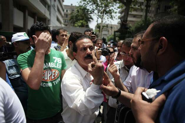 Egyptians argue during a protest near the Egyptian Parliament in Cairo, Egypt, Tuesday, June 19, 2012. The campaign of an Islamist who claimed victory in Egypt's presidential runoff says the Muslim Brotherhood and other political groups plan a mass demonstration later Tuesday to protest a military declaration seeking to curtail the powers of the next president. (AP Photo/Manu Brabo) Photo: Manu Brabo