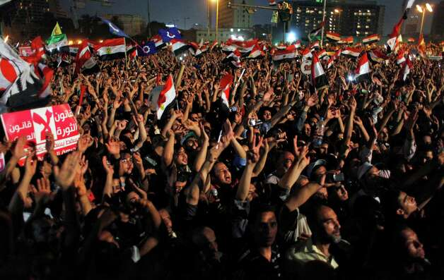 "Egyptian Muslim Brotherhood supporters wave national flags and chant slogans, and one carries a banner that reads in Arabic ""The law of the revolution not the law military,"" during an anti-ruling military council demonstration in Tahrir Square, Cairo, Egypt Tuesday, June 19, 2012. The campaign of Hosni Mubarak's former prime minister said on Tuesday he has won Egypt's presidential election, not the rival Muslim Brotherhood's candidate, opening a potential fight for the post and adding a new layer to the country's unrest and political power struggles. (AP Photo/Nasser Nasser) Photo: Nasser Nasser"