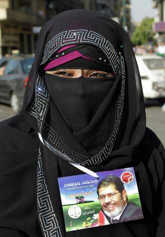 "An Egyptian supporter of Muslim brotherhood candidate Mohammed Morsi wears a tag with Arabic that reads, ""'Mohammed Morsi, president for Egypt"" in Tahrir Square, Cairo, Monday, June 18, 2012. Egypt's ruling military council pledged Monday to honor its promise to hand over power to the newly elected president by the end of this month, hours after Islamist candidate Mohammed Morsi claimed victory in the first free presidential vote since the ouster of authoritarian leader Hosni Mubarak 16 months ago.  (AP Photo/Amr Nabil) Photo: Amr Nabil"