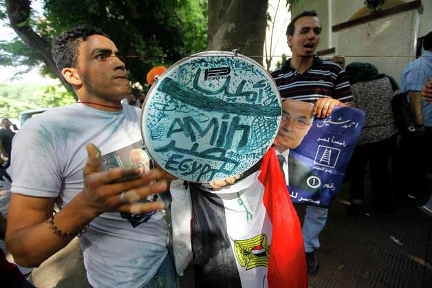 "Supporters  of presidential candidate Ahmed Shafiq hold posters of him with Arabic that reads, ""Ahmed Shafiq, for Egyptian presidency,"" in front of his campaign headquarters in Cairo, Egypt, Tuesday, June 19, 2012. A campaign spokesman for Hosni Mubarak's ex-prime minister said on Tuesday that Ahmed Shafiq has won the Egyptian presidential election, countering the Muslim Brotherhood's claims that its candidate was the winner.  (AP Photo/Amr Nabil) Photo: Amr Nabil"