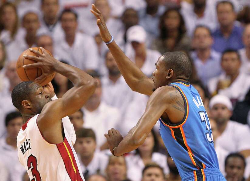 Dwyane Wade of the Miami Heat looks to pass against Kevin Durant of the Oklahoma City Thunder during