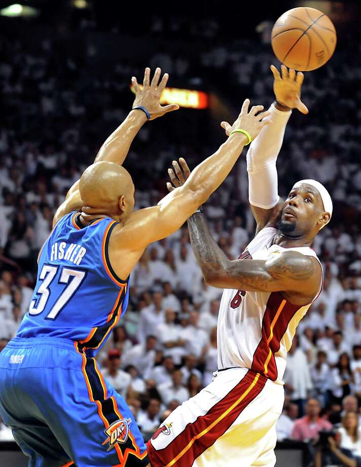 Game 4: Heat 104, Thunder 98 (Heat leads series 3-1) - LeBron James of the Miami Heat passes the ball while being guarded by Oklahoma City Thunder's Derek Fisher in the second quarter during Game 4 of the NBA Finals at the AmericanAirlines Arena in Miami. Photo: Robert Duyos, McClatchy-Tribune News Service / Sun Sentinel