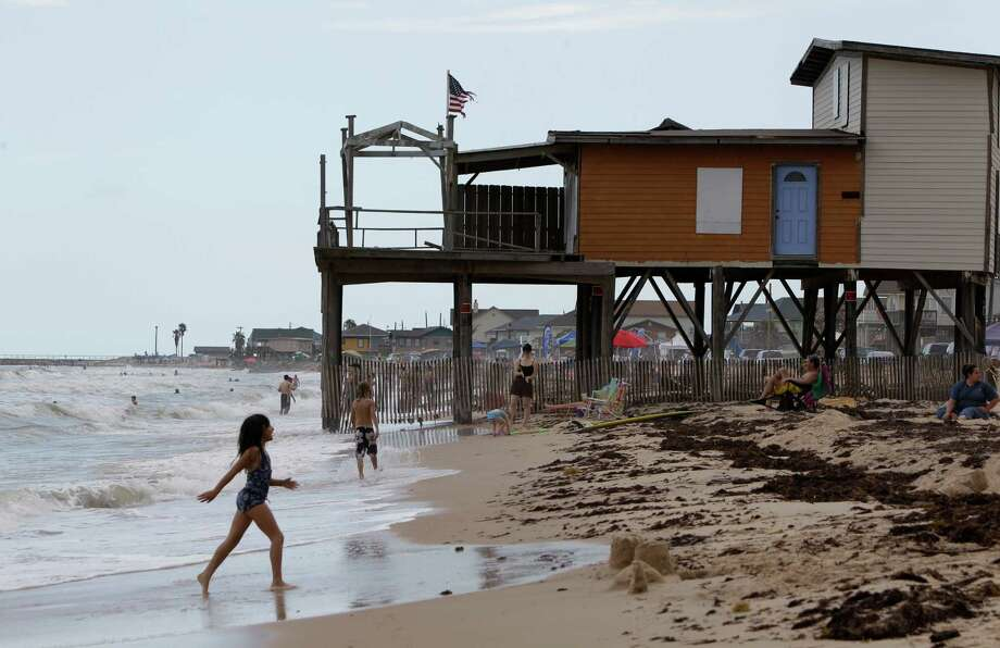 Beach goers pass one of  two storm-battered houses that remain along Beach Drive in Surfside, Saturday, June 16, 2012.  The Texas Open Beaches Act is becoming a topic in the Texas Supreme Court races.  ( Melissa Phillip / Houston Chronicle ) Photo: Melissa Phillip / © 2012 Houston Chronicle