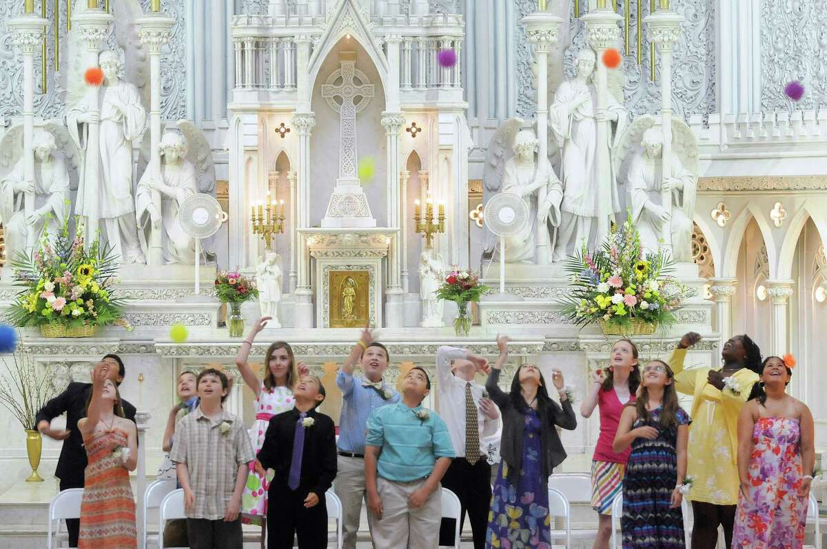 Sixth-grade students throw balls into the air at the conclusion of a ceremony for the final graduation of students from St. John the Evangelist School on Tuesday, June 19, 2012 in Schenectady, NY. The diocese is closing the school because of declining enrollment. (Paul Buckowski / Times Union)