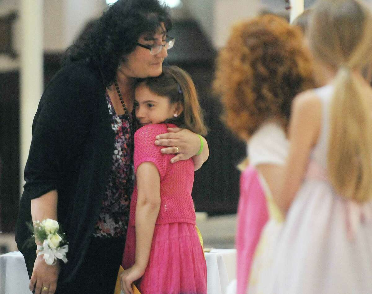 Teacher Gina Alvord hugs her third-grade student Jennifer Canale, 9, during a ceremony for the final graduation of students from St. John the Evangelist School on Tuesday, June 19, 2012 in Schenectady, NY. The diocese is closing the school because of declining enrollment. Alvord has been teaching at the school for 23 years. (Paul Buckowski / Times Union)