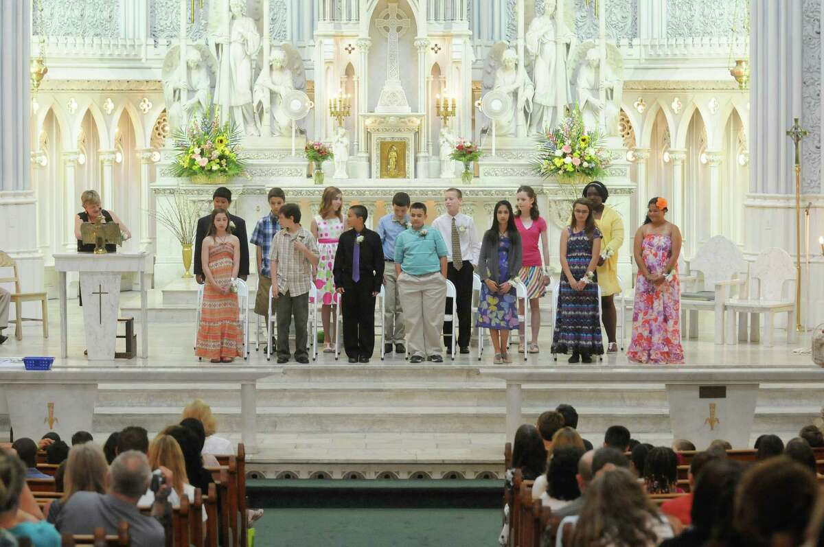 Sixth-grade students stand as Principal Marie Keenan, left, talks about each one during a ceremony for the final graduation of students from St. John the Evangelist School on Tuesday, June 19, 2012, in Schenectady, NY. The diocese is closing the school because of declining enrollment. (Paul Buckowski / Times Union)