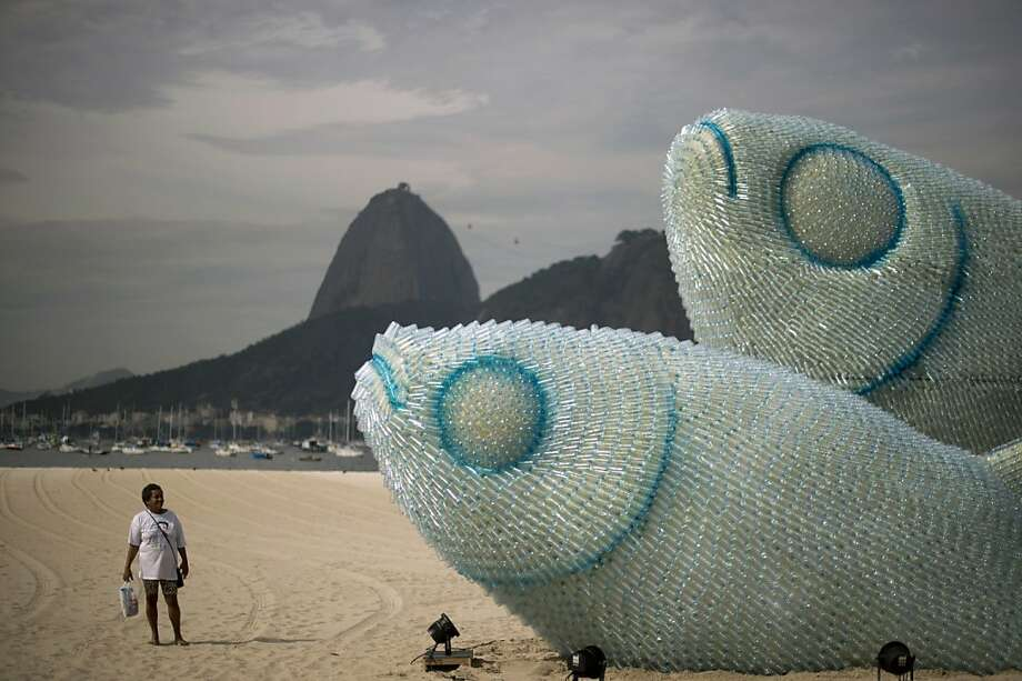 A woman looks at an installation made of recycled plastic bottles representing fishes, in Botafogo beach, in Rio de Janeiro, on June 19, 2012, in the sidelines of the UN Conference on Sustainable Development, Rio+20. The UN conference, which marks the 20th anniversary of the Earth Summit -- a landmark 1992 gathering that opened the debate on the future of the planet and its resources -- is the largest ever organized, with 50,000 delegates.  AFP PHOTO / Christophe SimonCHRISTOPHE SIMON/AFP/GettyImages Photo: Christophe Simon, AFP/Getty Images