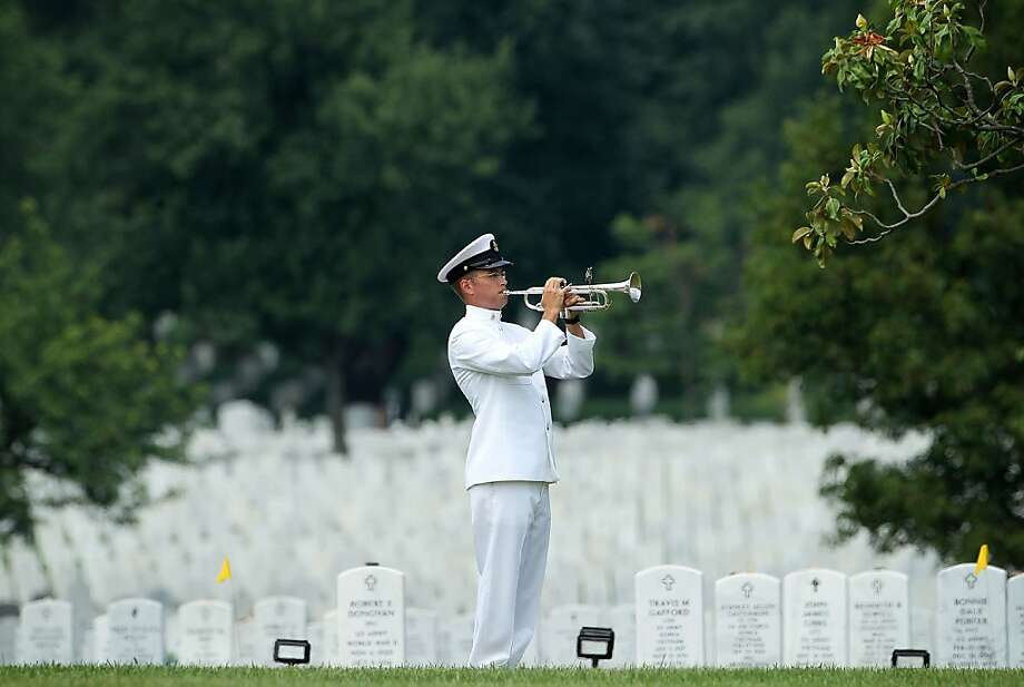 """ARLINGTON, VA - JUNE 19:  Bugler Gunnar R. Bruning plays """"Taps"""" during the burial of U.S. Navy Petty Officer 2nd Class Sean E. Brazas June 19, 2012 at Arlington National Cemetery in Arlington, Virginia. Petty Officer Brazas, a K-9 handler, was killed while being ambushed as he was helping a fellow officer into a helicopter in Panjaw'l, Afghanistan on May 30, 2012.  (Photo by Alex Wong/Getty Images) Photo: Alex Wong, Getty Images"""