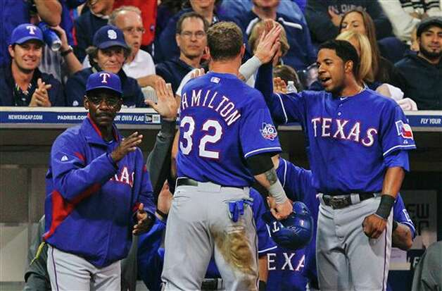 Texas Rangers' Josh Hamilton is greeted by manager Ron Washington and teammates after scoring against the San Diego Padres during the fourth inning of an interleague  baseball game Tuesday, June 19, 2012 in San Diego. (AP Photo/Lenny Ignelzi) Photo: Associated Press