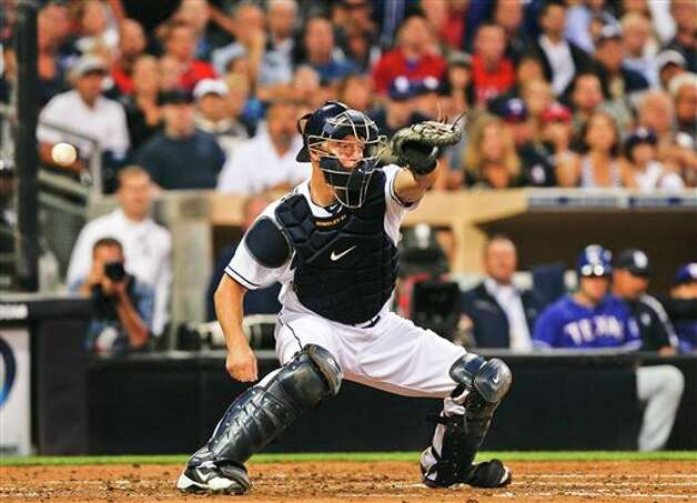 San Diego Padres catcher Nick Hundley misses the ball on a throw from right field trying to catch Texas Rangers' Josh Hamilton trying to score during the third inning of  an interleague  baseball game Tuesday, June 19, 2012 in San Diego. (AP Photo/Lenny Ignelzi) Photo: Associated Press
