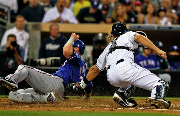 Texas Rangers' Josh Hamilton slides past the attempted tag by San Diego Padres catcher Nick Hundley while scoring on a sacrifice fly by Adrian Beltre during the third inning of an interleague  baseball game Tuesday, June 19, 2012 in San Diego. Hundley attempted the tag without the ball. (AP Photo/Lenny Ignelzi) Photo: Associated Press