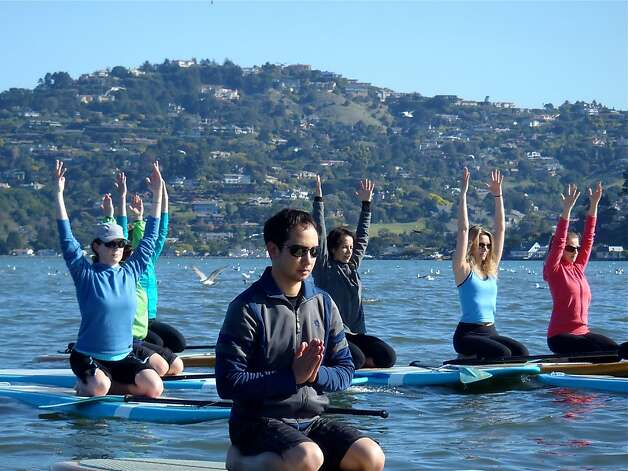 Students practice stand up paddle yoga, known among practitioners as SUP Yoga. Photo: Leigh Claxton