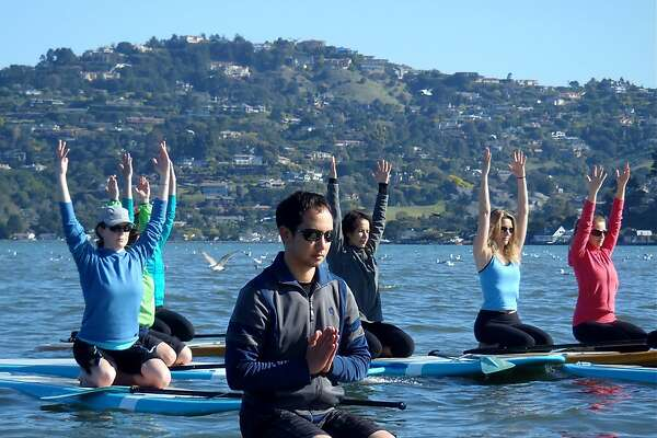 Students practice stand up paddle yoga, known among practitioners as SUP Yoga.