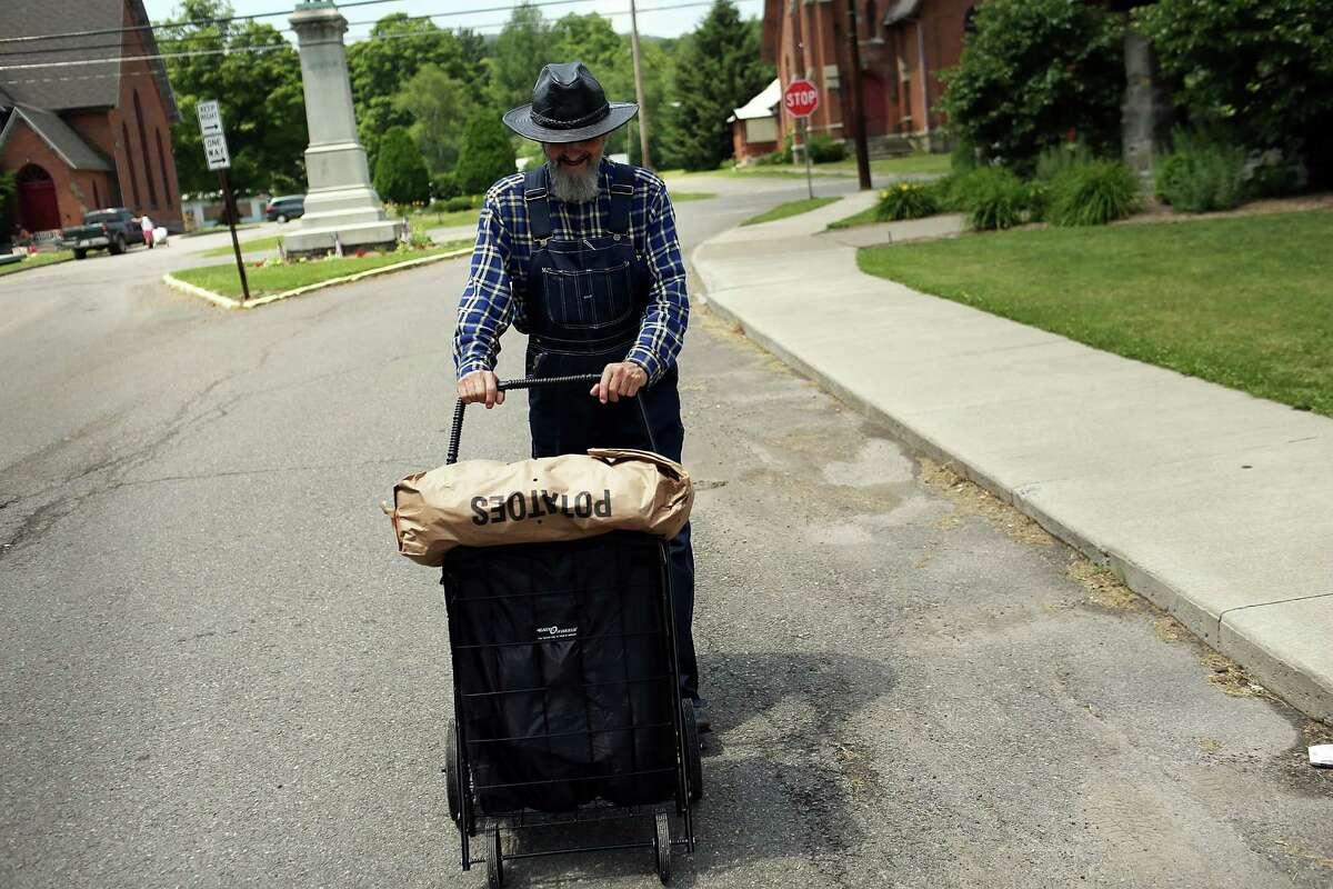 DEPOSIT, NY - JUNE 19: Joseph Smith walks down a road with a basket of food that was handed out by the Food Bank of the Southern Tier Mobile Food Pantry on June 19, 2012 in Deposit, New York. The mobile food pantry program was introduced in 2007 in the Southern Tier of New York and covers nearly 4,000 predominately rural miles. The converted beverage truck delivers fresh produce, dairy products and other grocery items to individuals and families in need. The pantry typically distributes for a period of two hours and provides 100 to 160 families with food. According to the 2010 Census, 15.72% the population serviced by the mobile pantry live at or below the federal poverty level.