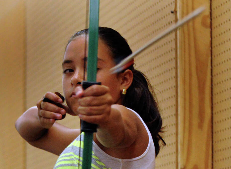 Archery teaches youngsters self-discipline and patience, fans of the sport say. Here, Genina Villarreal shoots during a lesson at Gassman's Archery. Photo: Billy Calzada, San Antonio Express-News / © 2012 San Antonio Express-News
