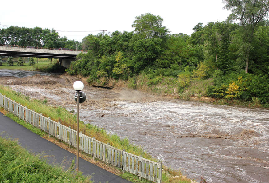 The Cannon River rushes through Cannon Falls, Minn., Friday June 15, 2012, after rains pummeled sout