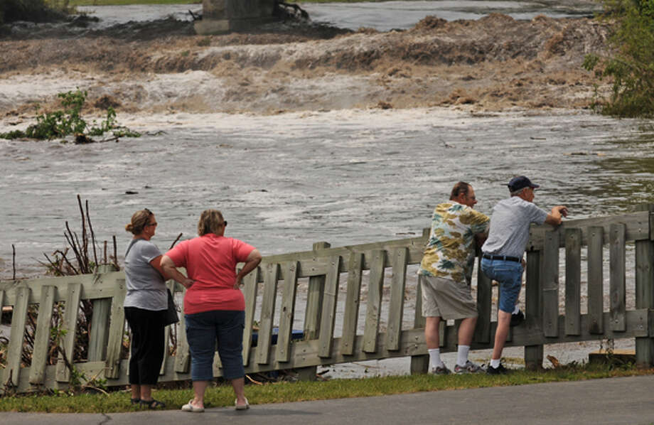 People look over the flooding of the Cannon and Little Cannon rivers, Friday June 15, 2012, in Cannon Falls, Minn. Residents in roughly two dozen homes  were asked to evacuate after heavy rains sent the Cannon River and the Little Cannon River rising, while residents in the southern part of Goodhue County were cleaning up damage caused by winds ranging from 60 to 80 mph. (AP Photo/The Star Tribune, Richard Sennott)  MANDATORY CREDIT; ST. PAUL PIONEER PRESS OUT; MAGS OUT; TWIN CITIES TV OUT Photo: .