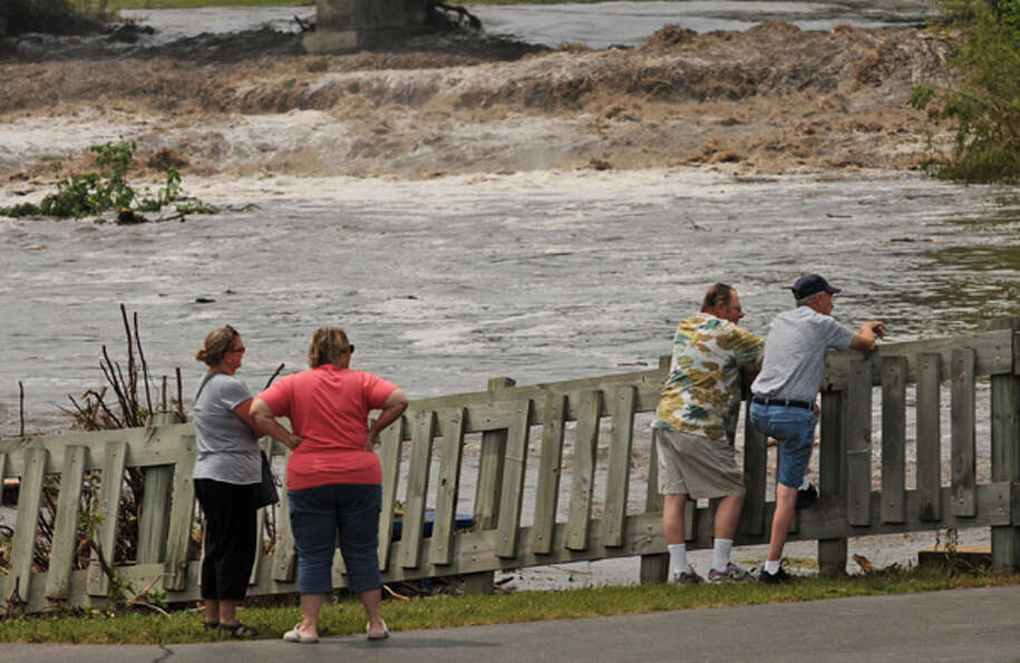 People look over the flooding of the Cannon and Little Cannon rivers, Friday June 15, 2012, in Canno
