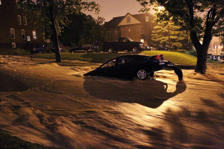 A car is stranded in floodwaters rushing down a hillside in Duluth, Minn., early Wednesday, June 20, 2012. Hours of torrential rainfall have sparked major flooding across the city and along the North Shore of Lake Superior, with some homes being evacuated due to rising water. Photo: .