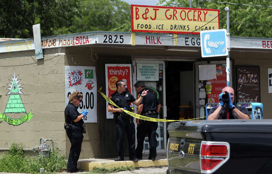 San Antonio Police work the scene of a robbery on Tuesday, June 19, 2012, at the B&J Grocery in the 2800 block of Chihuahua Street. According to San Antonio Police Sgt. James Prendergast, the robbery suspect got into a scuffle with the store clerk, who shot at the suspect. The suspect fled on foot about a block away to 2100 block of Santiago where police caught up with him. He was later transported to University Hospital with injuries not considered life-threatening. Photo: John Davenport, San Antonio Express-News