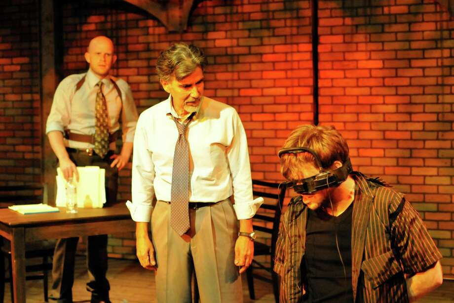 "Tyler Keyes (from left) and Roger Alvarez play cops investigating a writer (Michael Burger) in the Woodlawn Black Box Theatre's staging of ""The Pillowman."" Photo: Courtesy, Sandra Trevino"