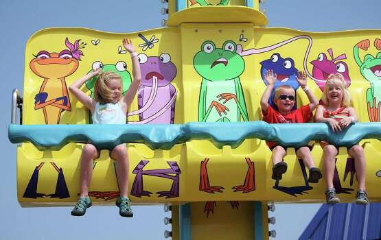 Kansas City visitors Madeline Hammett, 9, left, rides the Frog Hopper ride with her brother, Benjamin, 4, and sister Caroline, 6 at the new Pleasure Pier, May 25, 2012, in Galveston. ( Karen Warren / Houston Chronicle ) Photo: Karen Warren / 2012  Houston Chronicle