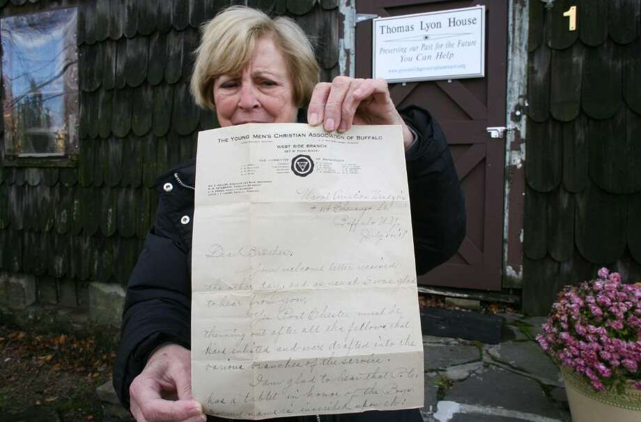 Greenwich Preservation Trust Chairwoman Jo Conboy holds one of the  many letters written by soldiers in the first World War outside the Lyons House on West Putanam Avenue where it was found. Photo: David Ames / Greenwich Time