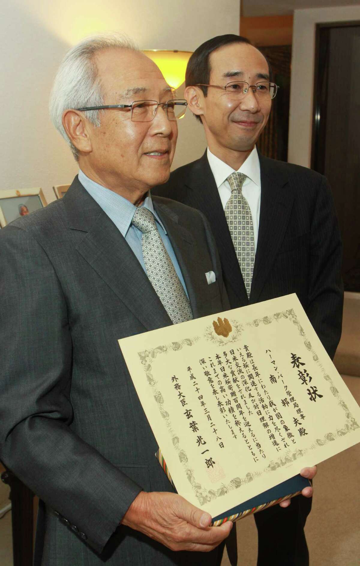Honoree Kunio Minami, holding the Japanese Foreign Minister's commendation, left, and Consul General Jota Yamamoto
