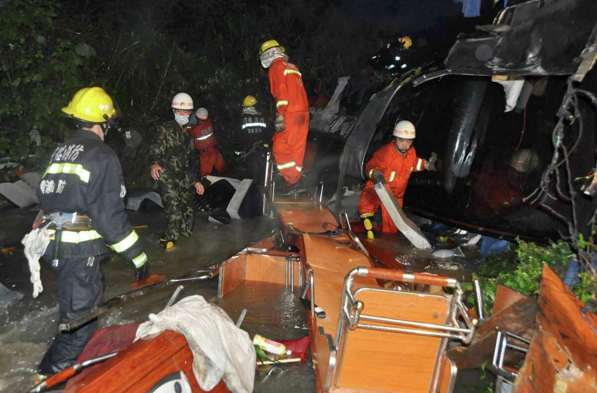 Firefighters search for survivors in the wreckage of a passenger bus that crashed into a valley in Xiafu, southern China's Fujian province on Wednesday. Seventeen people were killed and three others severely injured of the 45 passengers on the bus. ( STR/AFP/GettyImages)