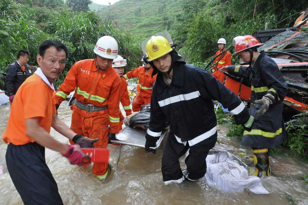 Firefighters carry a victim's body that was found in the wreckage of a passenger bus that crashed into a valley in Xiafu, southern China's Fujian province on Wednesday. Seventeen people were killed and three others severely injured of the 45 passengers on the bus. (STR/AFP/GettyImages)