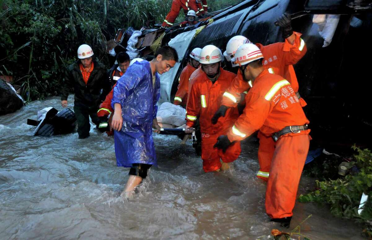 Firefighters carry a victim's body that was found in the wreckage of a bus that crashed into a valley in Xiafu, southern China's Fujian province on Wednesday. Seventeen people were killed and three others severely injured of the 45 passengers on the bus. (STR/AFP/GettyImages)