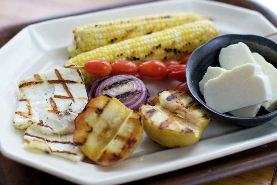 This image taken on Sept. 8, 2011 shows a recipe using the Greek grilling cheese, Halloumi, in a salad combined with grilled corn, apples and onions served on a platter, in Concord, N.H. (AP Photo/Matthew Mead) Photo: Matthew Mead