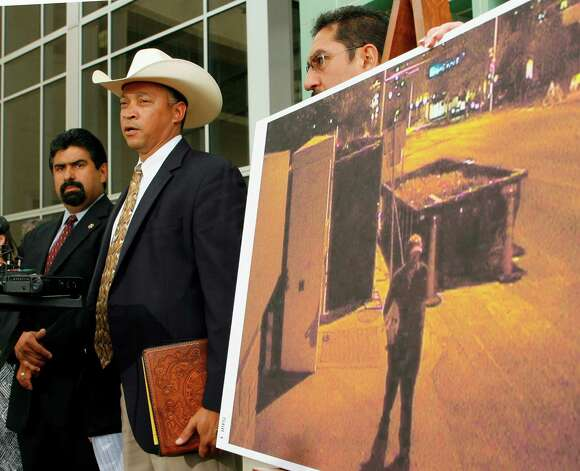 Texas Rangers Lt. Alvin Alexis, center, the lead investigator in the torching of the Governor's Mansion, speaks during a news conference Tuesday, July 29, 2008, in Austin, Texas.  He discussed the release of security camera video, a frame of which is enlarged and shows a person of interest related to the June 8 blaze that damaged the 152-year-old building. Michael Reyes, left is the ATF Austin resident agent in charge. State Fire Marshal Paul Maldonado is on the right. Photo: Harry Cabluck, AP / AP