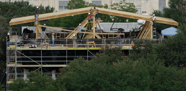 "Construction workers erect a temporary roof over the Texas Governor's Mansion Thursday, Sept. 11, 2008, in Austin, Texas. The historic building was torched early Sunday, June 8, 2008. It left much of the home charred and inflicted damage that state officials described as ""bordering on catastrophic.""  The unoccupied mansion had been undergoing a $10 million renovation. Photo: Harry Cabluck, AP / AP"