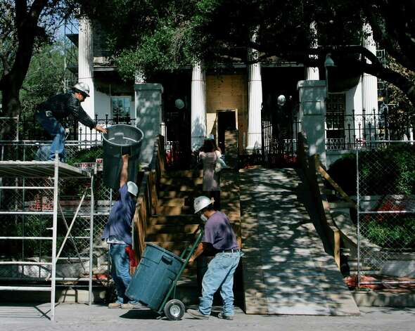 Workers remove debris from the fire-damaged Texas Governor's Mansion Monday, June 16, 2008, in Austin, Texas. A $50,000 reward is being offered for information leading to an arrest in the fire that badly damaged the mansion. Photo: Harry Cabluck, AP / AP