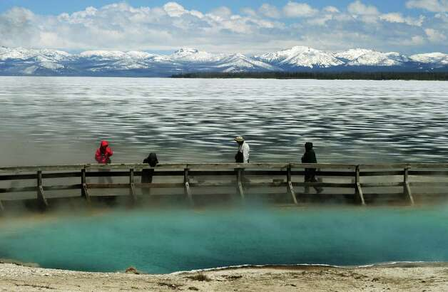 Tourists walk beside a hot spring and the partially frozen Yellowstone Lake at the West Thumb Geyser Basin in the Yellowstone National Park, Wyoming on June 2, 2011.  Yellowstone National Park, was established by the U.S. Congress and signed into law by President Grant on March 1, 1872. The park is located primarily in the U.S. state of Wyoming, though it also extends into Montana and Idaho and was the first national park in the world. It is known for its wildlife and its many geothermal features, especially the Old Faithful Geyser.          TOPSHOTS             AFP PHOTO/Mark RALSTON (Photo credit should read MARK RALSTON/AFP/Getty Images) Photo: MARK RALSTON / AFP