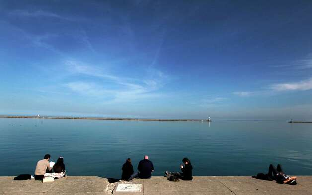 Small groups of people gather on the Lake Michigan waterfront at DuSable Harbor Tuesday, March 13, 2012, in Chicago. Temperatures inch closer to March record highs after a mild winter. (AP Photo/Charles Rex Arbogast) Photo: Charles Rex Arbogast / AP