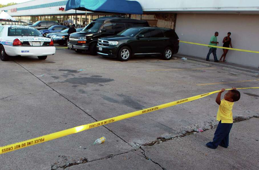 A toddler plays with crime scene tape as police investigate a homicide where three people were shot