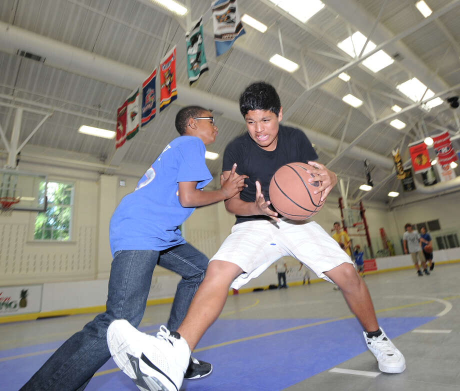 At right, Jose Romero, 13, of Greenwich, drives to the basket during a game of one-on-one against friend, Zhaire House, also 13, also of Greenwich, at the Boys & Girls Club of Greenwich, Friday, June 15, 2012. Photo: Bob Luckey / Greenwich Time