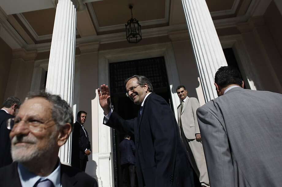 Greece's newly sworn-in Prime Minister Antonis Samaras, center, gestures to supporters after taking over from caretaker Prime Minister Panayiotis Pikramenos, not seen, at Maximos Mansion, Athens, Wednesday, June 20, 2012. Samaras was sworn in as prime minister Wednesday at the helm of a three-party coalition that will uphold the country's international bailout commitments. (AP Photo/Kostas Tsironis) Photo: Kostas Tsironis, Associated Press